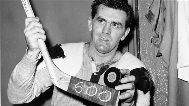 Maurice Richard montre la rondelle du 600e but de sa carrière dans la Ligue nationale, en comptant les séries.