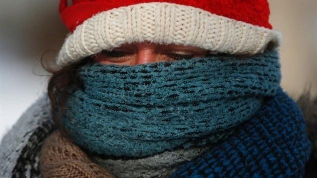 Une femme se pare contre le grand froid comme elle peut.