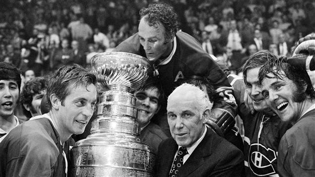 Jean Béliveau (à gauche) et Henri Richard (en haut) reçoivent des mains du commissaire Clarence Campbell la coupe Stanley, le 18 mai 1971.