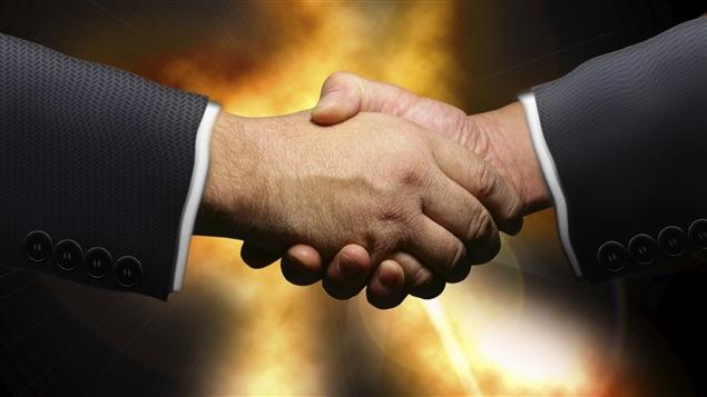 Deux hommes échangent une poignée de main.
