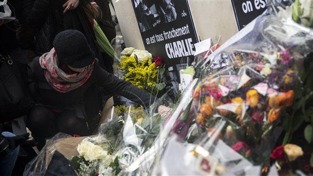 Une femme dépose des fleurs devant les locaux de Charlie Hebdo.