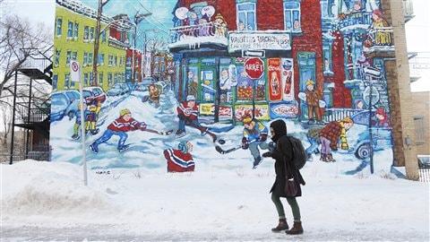 Une piétonne marche devant une murale d'une scène d'hiver à Montréal.