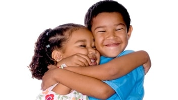Deux enfants échangent un câlin.