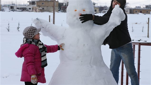 A Syrian man and his daughter make a snowman at a refugee camp in al-Majdal village, Bekaa Valley, East Lebanon on Jan. 8, 2015. A powerful winter storm swept through the region, killing several Syrian refugees in Lebanon and forcing thousands of others who have fled their country's civil war to huddle together for warmth.