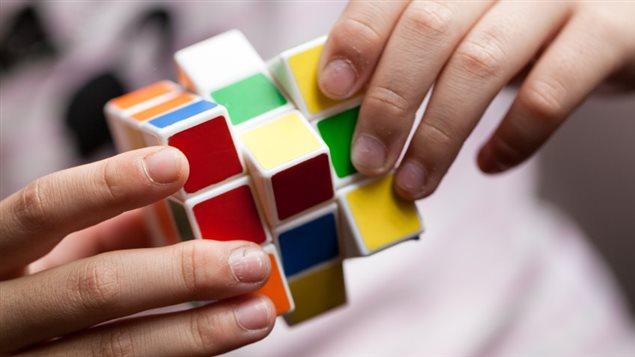 Une personne tente de résoudre un cube Rubik.