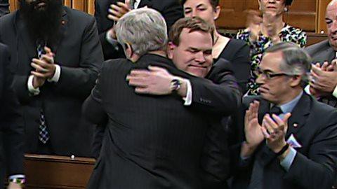 John Baird reçoit l'accolade du premier ministre Harper après l'annonce de son départ de la vue publique.