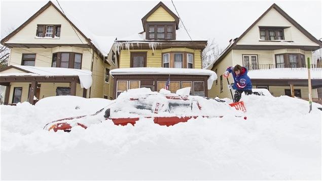 Une résidente de Buffalo tente d'extirper sa voiture d'un tas de neige.