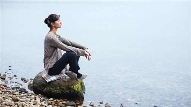 Une femme médite au bord d'un lac.