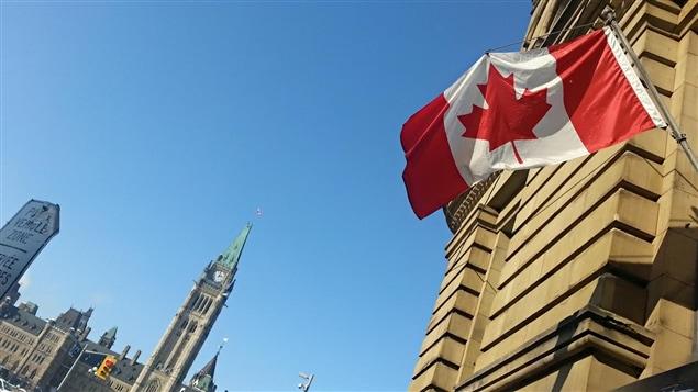 العلم الكندي يرفرف على أحد المباني أمام هضبة البرلمان في اوتاوا في 6 شباط فبراير 2015