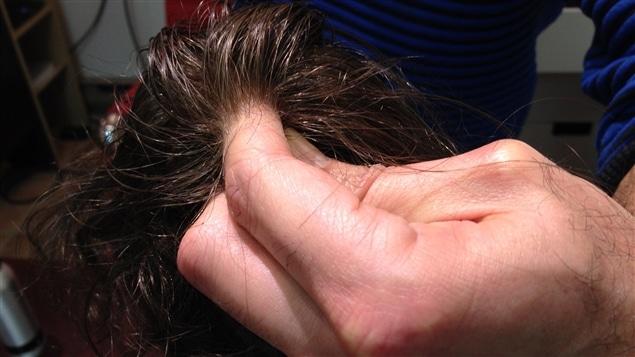 La minceur de la perruque présentée par Camille Toutounghi donne l'impression que les cheveux lui poussent sur les doigts.