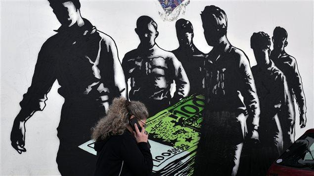 À Athènes, une femme passe devant un graffiti illustrant la mort de l'euro.