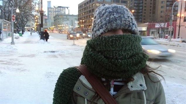 Une femme emmitouflée dans son écharpe se promène avenue Portage à Winnipeg durant l'hiver (archives).