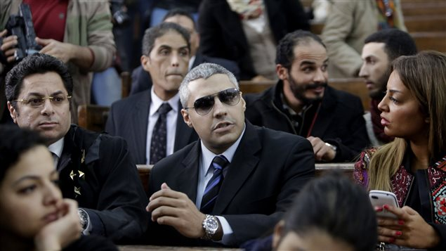 Canadian Al-Jazeera English journalist Mohamed Fahmy, centre, attends his retrial at a court in Cairo on Monday. The case was postponed to March 8. Mr. Fahmy, a who looks a bit like George Clooney, is seated in the courtroom surrounded by other people. He is dressed in a dark suit and is wearing dark sun glasses.