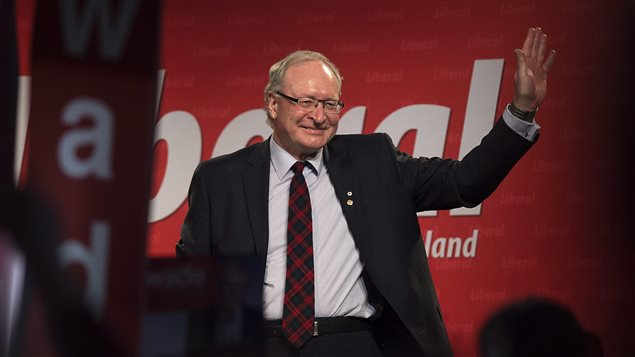 Wade MacLauchlan waves to the crowd as he is acclaimed leader at the Prince Edward Island Liberal leadership convention in Charlottetown on Saturday. We see the new premier, a handsome man with grey hair, standing with a smile on his face. He is wearing glasses and is dressed in a dark suit with the jacket open revealing a dark red plaid tie. He is waving with his left hand. Behind him is a red and white Liberal Party poster.