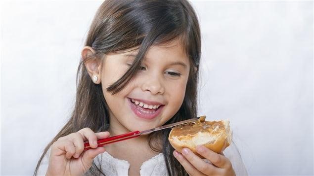 Une petite fille étend du beurre d'arachide sur un pain.