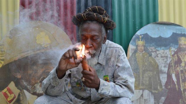 Bunny Wailer, légende du reggae et militant pour la décriminalisaion du cannabis, fume une pipe de marijuana durant une cérémonie rastarienne à Kingston, en Jamaïque, le 28 août 2014.