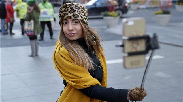 Une passante utilise une perche télescopique à Times Square, à New York