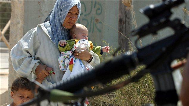 Una mujer palestina y sus hijos en un puesto de control del ejército israelí en Cisjordania