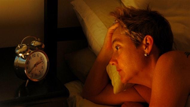 Une dame qui ne peu dormir regarde son reveil-matin
