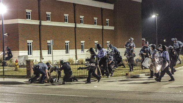 Des policiers se déploient après qu'un des leurs ait été blessé par balle, devant le poste de police de Ferguson