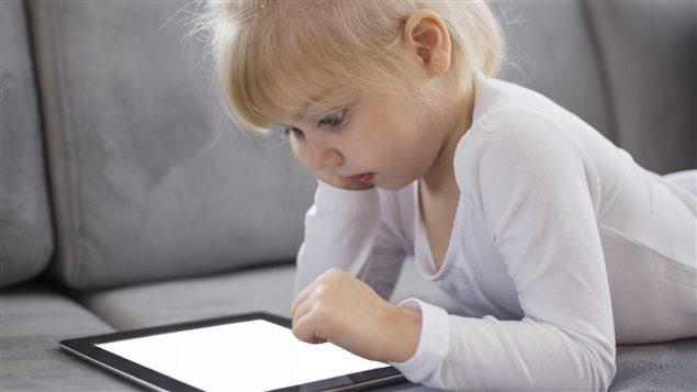 Une petite fille consulte une tablette numérique.