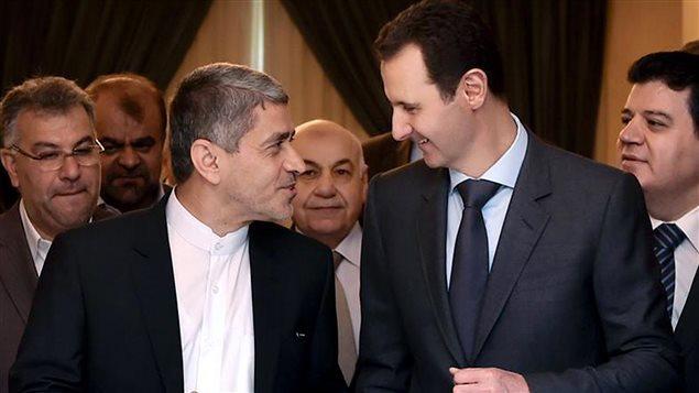 El presidente sirio Bachar Al-Assad conversando conel ministro iraní de la Economía, Ali Tayebnia.
