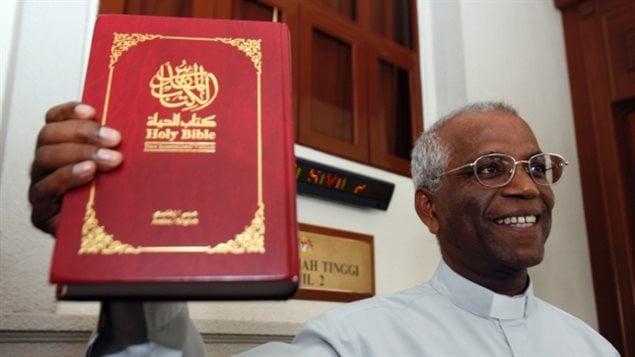Un prête catholique montre une bible écrite en langue arabe