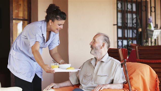 Une femme sert un repas à un homme en perte d'autonomie.