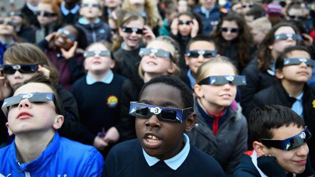 En Glascow, Escocia, niños observan un eclipse solar parcial, donde la Luna cubrió cerca de 75 % del Sol.