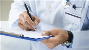 Un médecin remplit une fiche médicale.