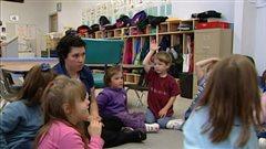 Une éducatrice et des enfants discutent dans un centre de la petite enfance.