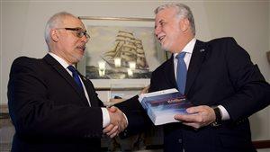 Le ministre des Finances du Québec, Carlos Leitao, remet une copie du budget 2015 au premier ministre Philippe Couillard.