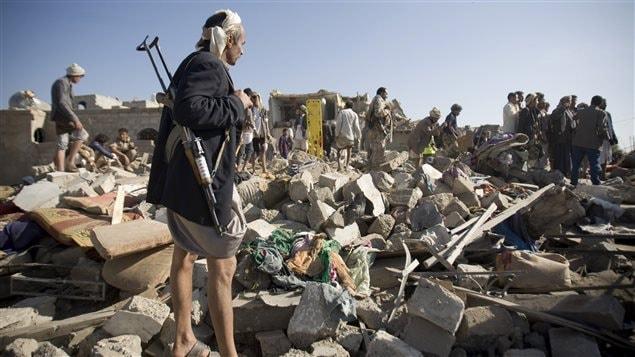 Un combattant houthi monte la gard ependant que des compagnons d'armes fouilles les décombres d'un immeuble détruit par un bombardement près de l'aéroport de Sanaa.