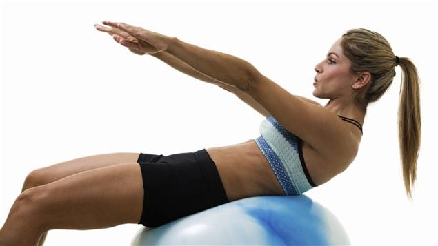 Une femme réalise une contraction abdominale sur un ballon suisse.