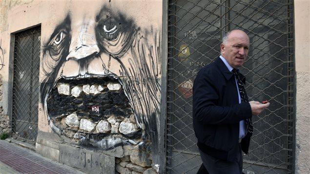 Un homme marche devant des boutiques abandonnées dans le quartier central d'Athènes, la capitale de la Grèce.