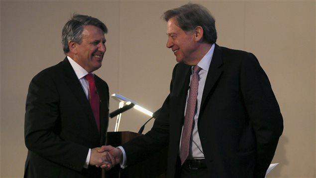 Ben van Beurden (gauche), président-directeur général de Royal Dutch Shell, serre la main d'Andrew Gould, président du conseil d'administration de BG Group, lors d'une conférence de presse, mercredi, à la Bourse de Londres.
