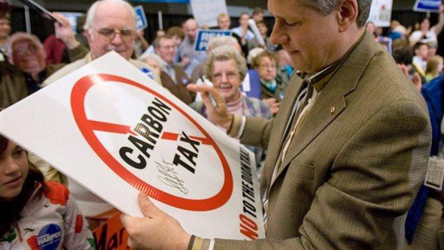 Le premier ministre canadien Stephen Harper avec entre les mains une enseigne contre la taxe au carbone lors d'un rassemblement de partisants conservateurs. Presse canadienne