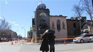 Des fidèles de la communauté grecque se recueillent devant l'église incendiée.