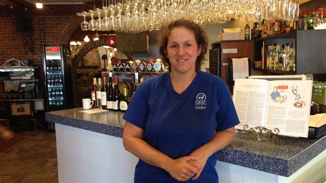 Ioanna Yannopoulos du restaurant grec Baie-Jolie pose à côté de l'article de <em>Caribou</em> qui lui est consacré