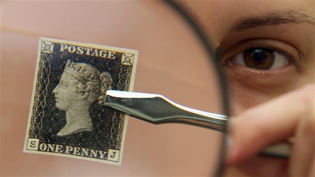 Un homme tient un timbre Penny Black à l'effigie de la reine Victoria, un des plus vieux timbres de l'histoire.