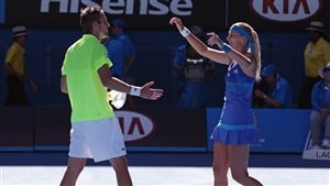 Daniel Nestor and Kristina Mladenovic of France celebrate their mixed doubles victory at the 2014 Australian Open. In Paris, they are seeking their third mixed doubles Grand Slam title together. We see Nestor on the left of the photo wearing a lime-green shirt and white tennis shorts about to embrace Mladenovic, who is wearing a stylish dark blue tennis dress. She has a long, blonde pony tail. They share looks of satisfaction mixed with their smiles.