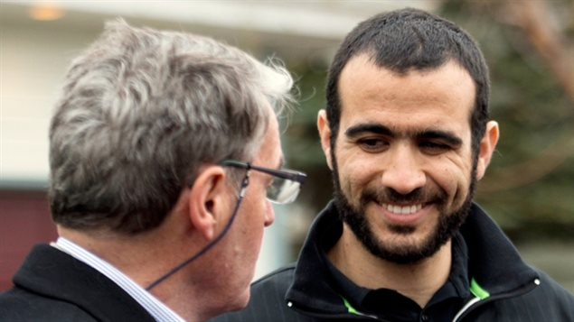 Omar Khadr, right, speaks to his lawyer Dennis Edney outside his new home after being granted bail in Edmonton on May 7. The bearded Khadr has short close-cropped black hair and his wearing a very big smile. The grey-haired Edney wears a dark suit and glasses.