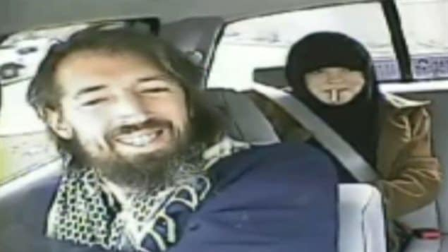 John Nuttall and Amanda Korody are charged with plotting to set off homemade bombs in British Columbia in 2013. We see the brown-bearded and shaggy-haired Nuttall in the front of a car. Behind him wearing a head-scarf is Korody