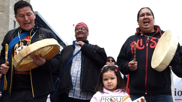 A child stands with drummers as they lead the Walk for Reconciliation with thousands or participants, part of the closing events of the Truth and Reconciliation Commission on Sunday in Ottawa. The commission uncovered horror stories of homemade electric chairs, malnutrition experiments and the deaths of more 6,000 children in residential schools.