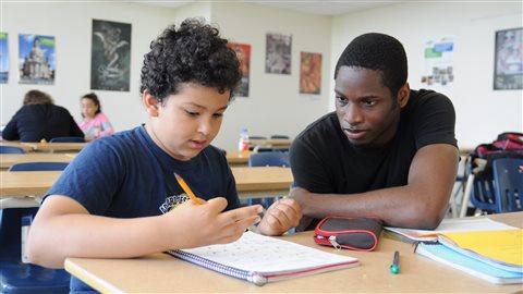 Jonathan Orélien, étudiant au cégep Marie-Victorin au Québec, aide Imran à faire son devoir de mathématique.