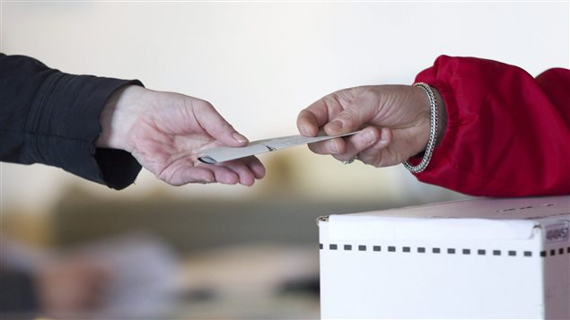 An election official hands back a marked ballot to voter so she can put it in the ballot box, in the federal election in May 2011.