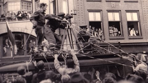 Standing on the roof of a Canadian designed Chev 8cwt van, (possibly one of the CBC vans, Sgt. Hugh McCaughey captures the euphoria on the streets of Utrecht on Victory in Europe Day in May 1945.