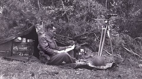 Sgt. Hugh McCaughey with film camera mounted on tripod, takes a bit of down time in France on June 30, 1944.