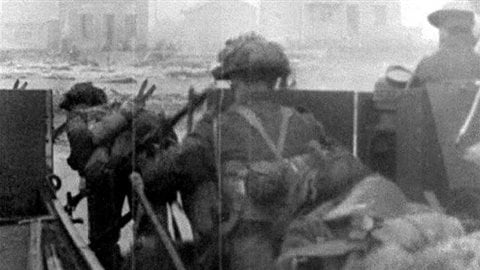 Scene from an CFPU 16mm film of Canadians landing at Juno beach early on June 6,  in the face of heavy fire from German defenders in the houses and built up fortifications. CFPU cameramen, usually in the front lines often faced the same danger as the armed soldiers
