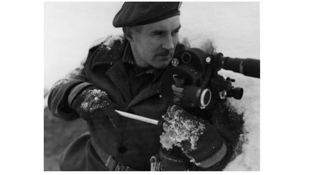 Sgt. Hugh McCaughey poses with his 35mm Bell & Howeel Eyemo camera.   30 Jan. 1945, Nijmegen, Netherlands.